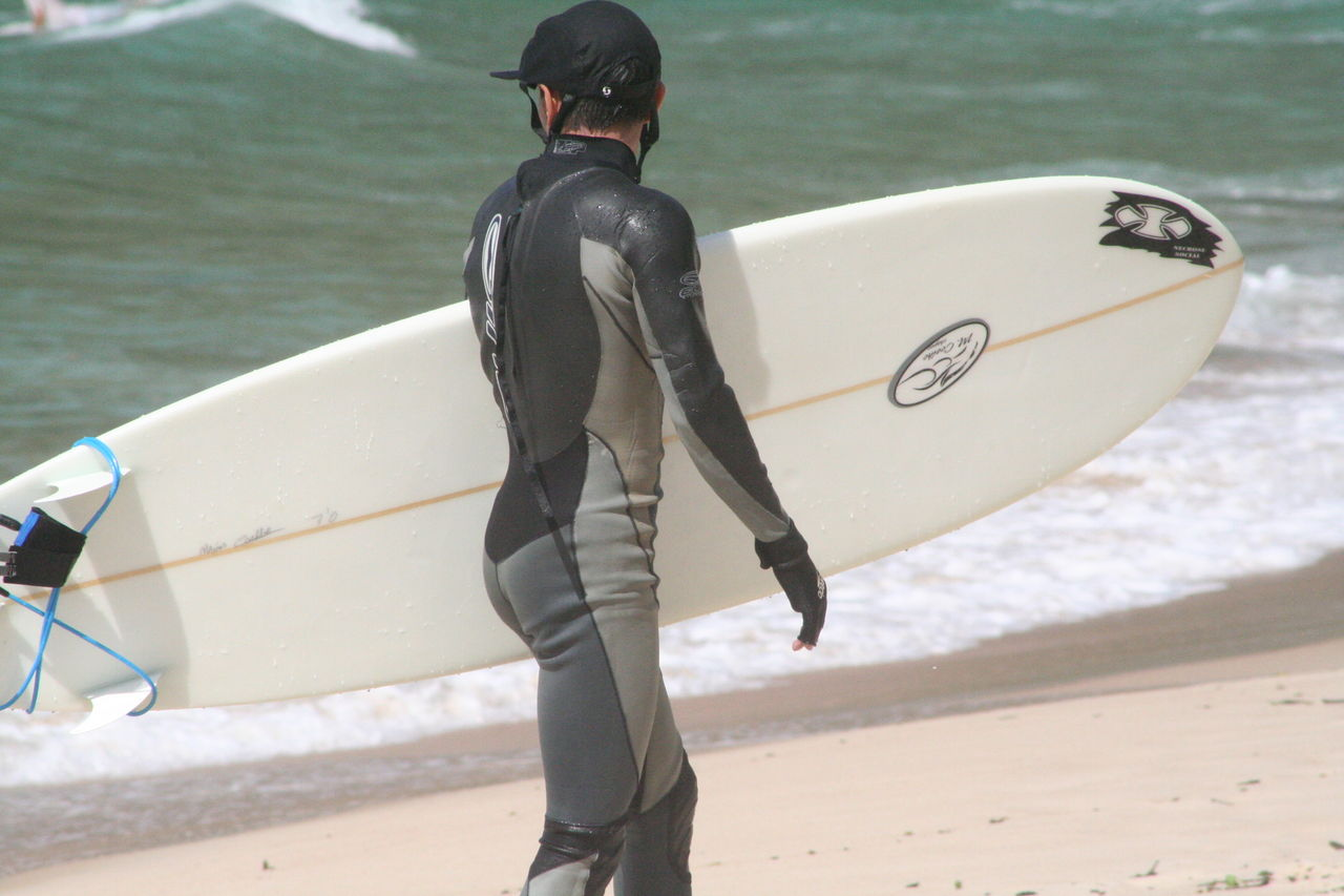 Файл:Surfer in wetsuit carries his surboard on the beach.JPG